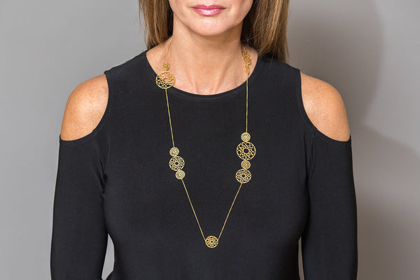 model wearing gold long necklace with spiral coins around neck layering