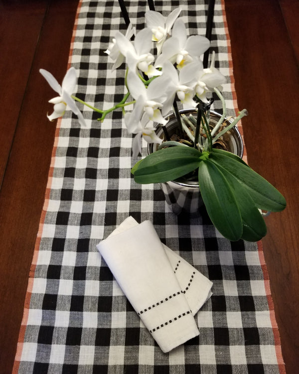 white cotton linen, black and white checkered table runner and orchid on table, handwoven in India