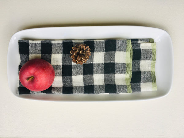 set of 4 chequered black and ivory handwoven napkins with a green edge placed on a plate with apple and a cone for presentation