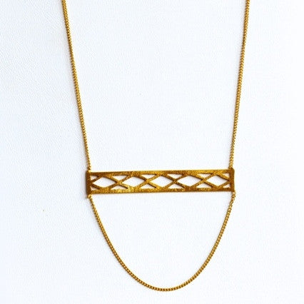 dainty gold necklace with criss cross patterned bar