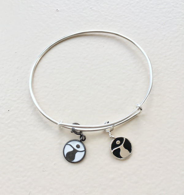 two empowered women charms on adjustable bracelet. one with black enamel and other with white enamel.  all sterling silver