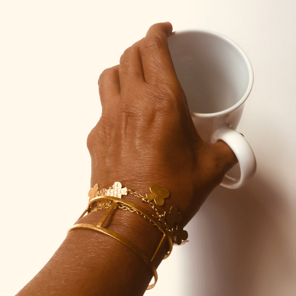 Model holding a cup while wearing the Gold Cuff - multiple bands and another bracelet by Thank You India