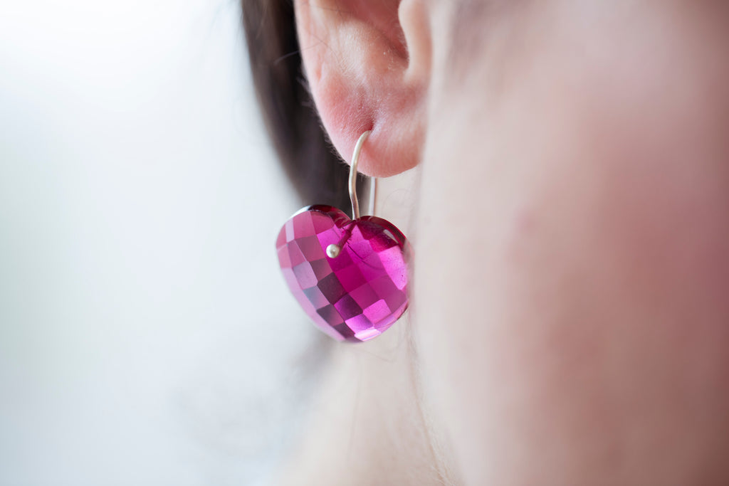Close up view on model wearing the Heart Earrings in pink by Thank You India