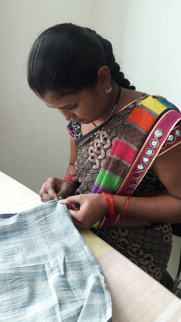 woman in textiles cooperative in Maheshwar, India hand sewing gray linen napkins