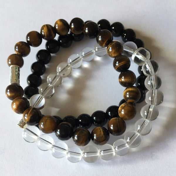 Pile of three stretchable bracelets with round beads made of semi-precious stones