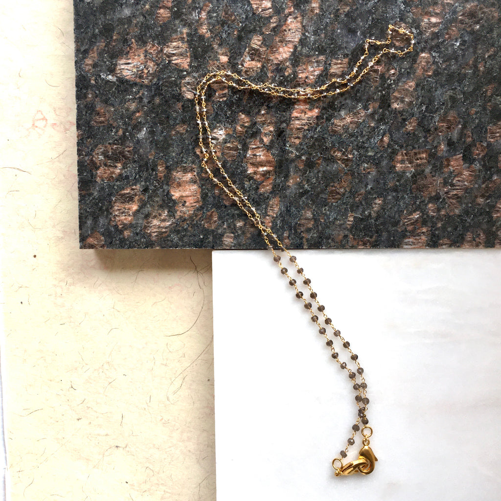 Close up shot of the Smoky Topaz Face Mask Chain & Necklace on marble by Thank You India