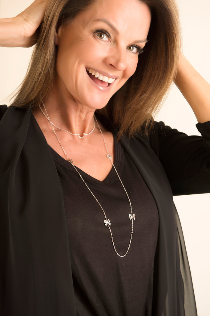 Model in black wearing the Two Tone Hopewell Butterfly Necklace and Minimal V Necklace all from Thank You India