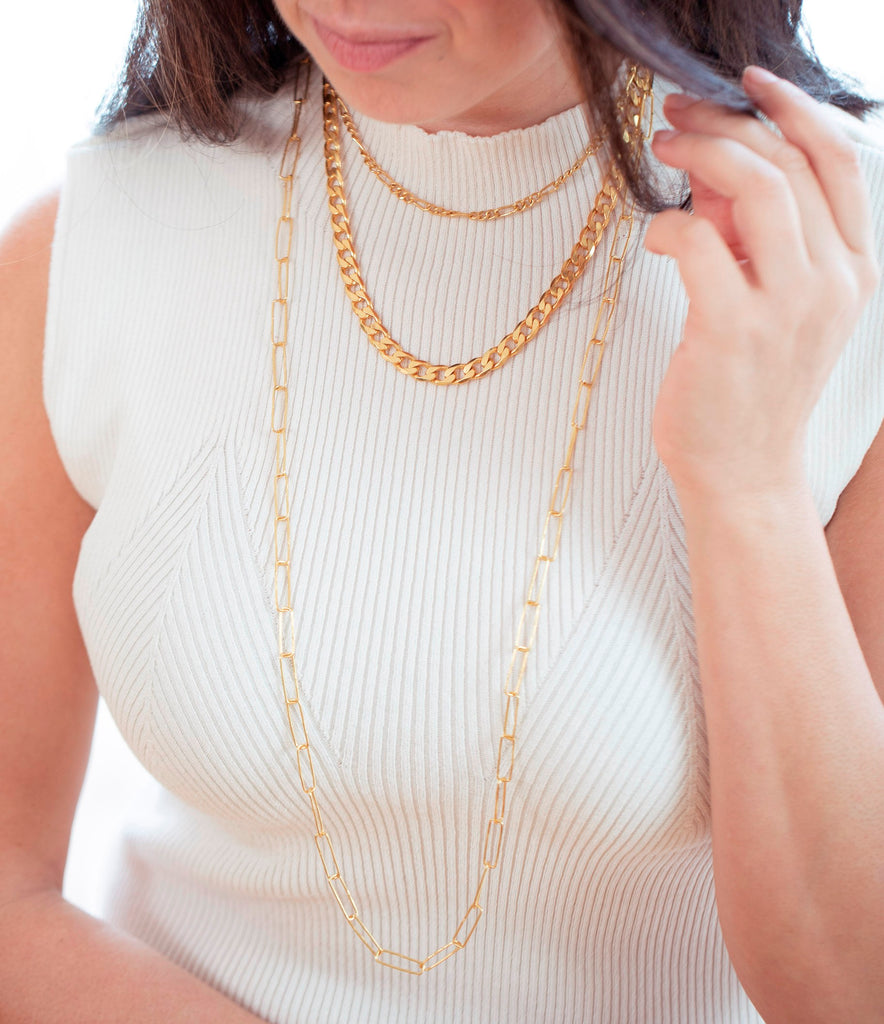 Model in white wearing figaro chain, Paperclip chain & curb chain all from Thank You India