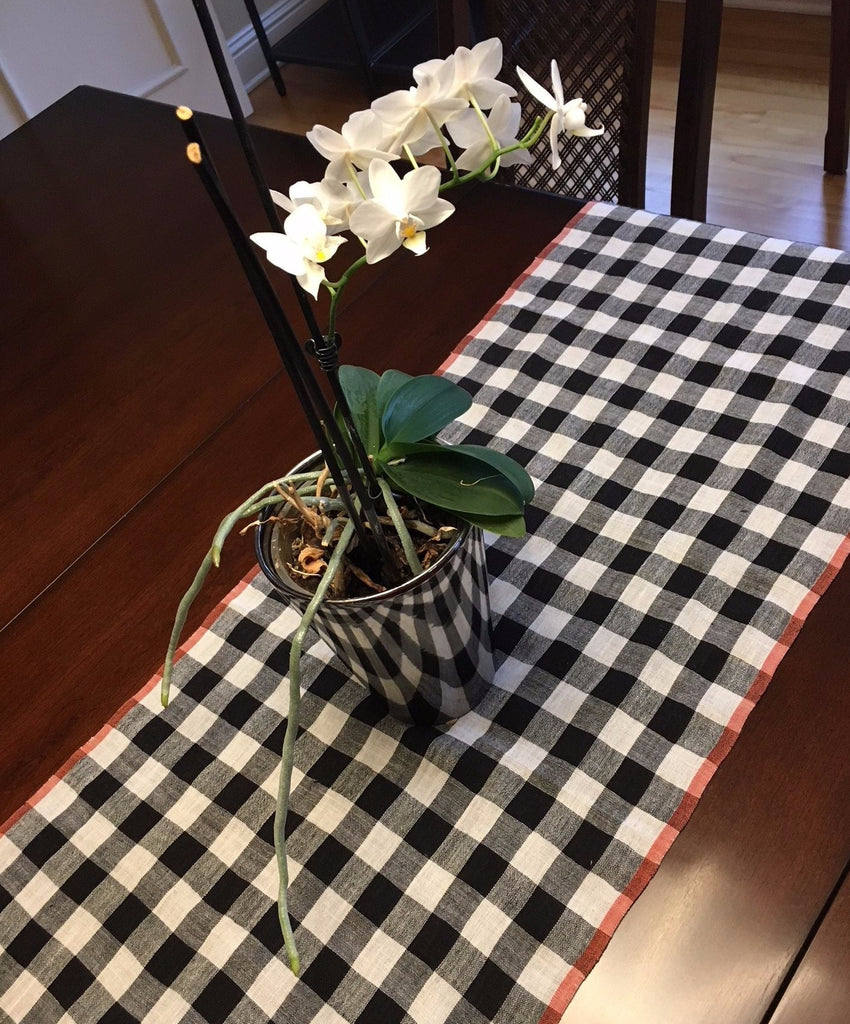 Black And White Checked Table Runner With Red Boarders On Table With Flowers