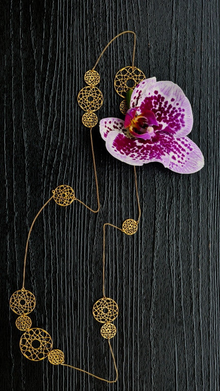 Gold Spiral Coins Necklace on table next to orchid flower