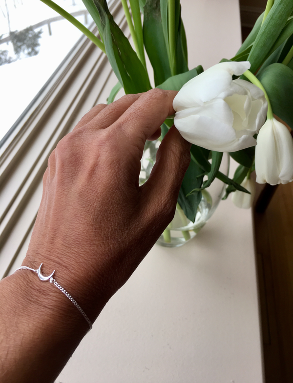 hand holding tulips with silver crescent bracelet on wrist