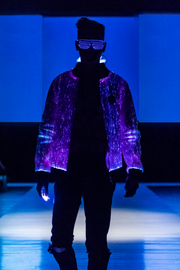 "Man wearing the Inlighten ""Prophecy Bomber,"" a fiber optic light up jacket (purple) for music festivals"
