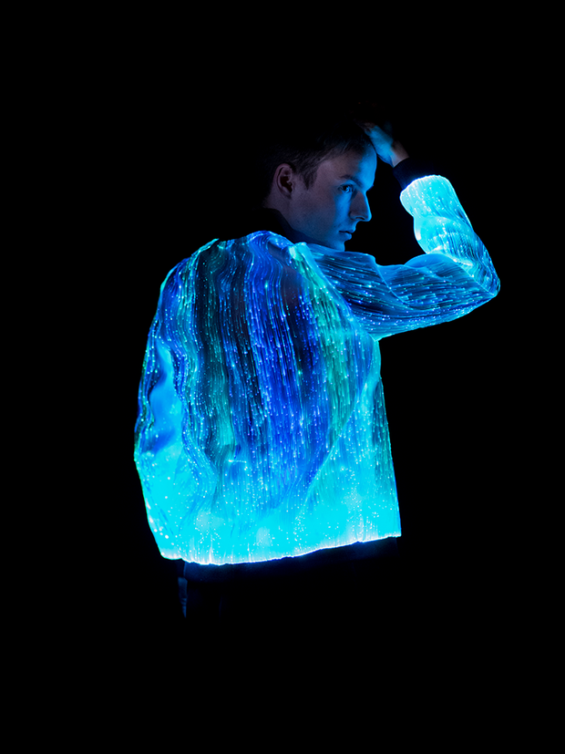 "Man wearing the Inlighten ""Prophecy Bomber,"" a fiber optic light up jacket (blue) for music festivals"