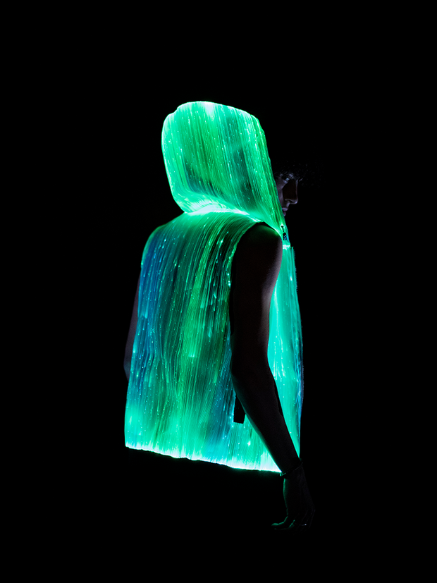 "Man wearing Inlighten ""Enhanced Revival Hoodie,"" a super bright fiber optic light up sleeveless hoodie (green) for music festivals"