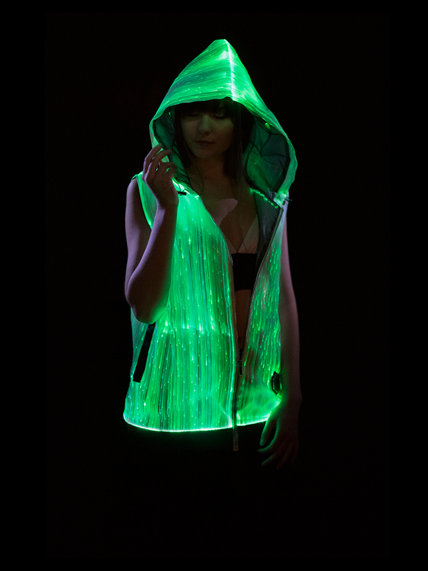 "Woman wearing Inlighten ""Enhanced Revival Hoodie,"" a super bright fiber optic light up sleeveless hoodie (green) for music festivals"