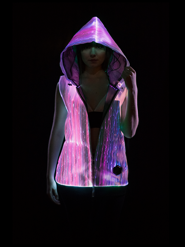 "Woman wearing Inlighten ""Enhanced Revival Hoodie,"" a super bright fiber optic light up sleeveless hoodie (pink) for music festivals"