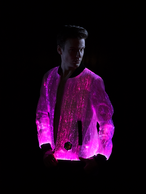 "Man wearing the Inlighten ""Prophecy Bomber,"" a fiber optic light up jacket (pink) for music festivals"
