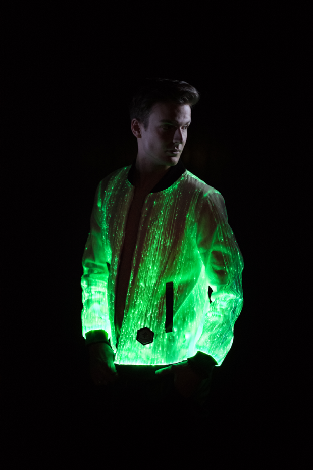 "Man wearing the Inlighten ""Prophecy Bomber,"" a fiber optic light up jacket (green) for music festivals"