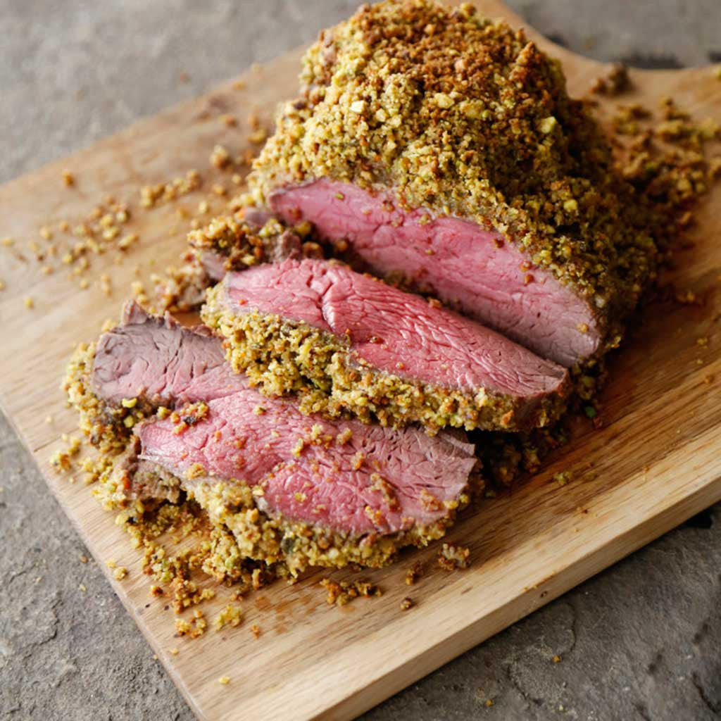 pistachio and Parmesan crusted beef tenderloin cooked perfectly to rare on a wooden cutting board