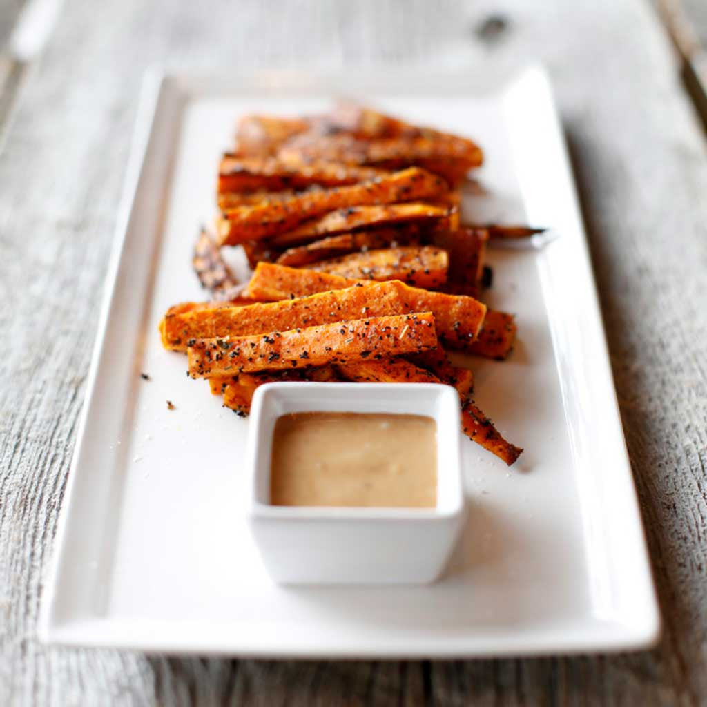 Coffee Roasted Sweet Potato Fries with Smoked Maple Aioli served on a white platter on a wooden table top.