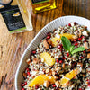 A colorful Pomegranate Citrus Quinoa Salad served in a white platter next to a bottle of tangerine white balsamic vinegar