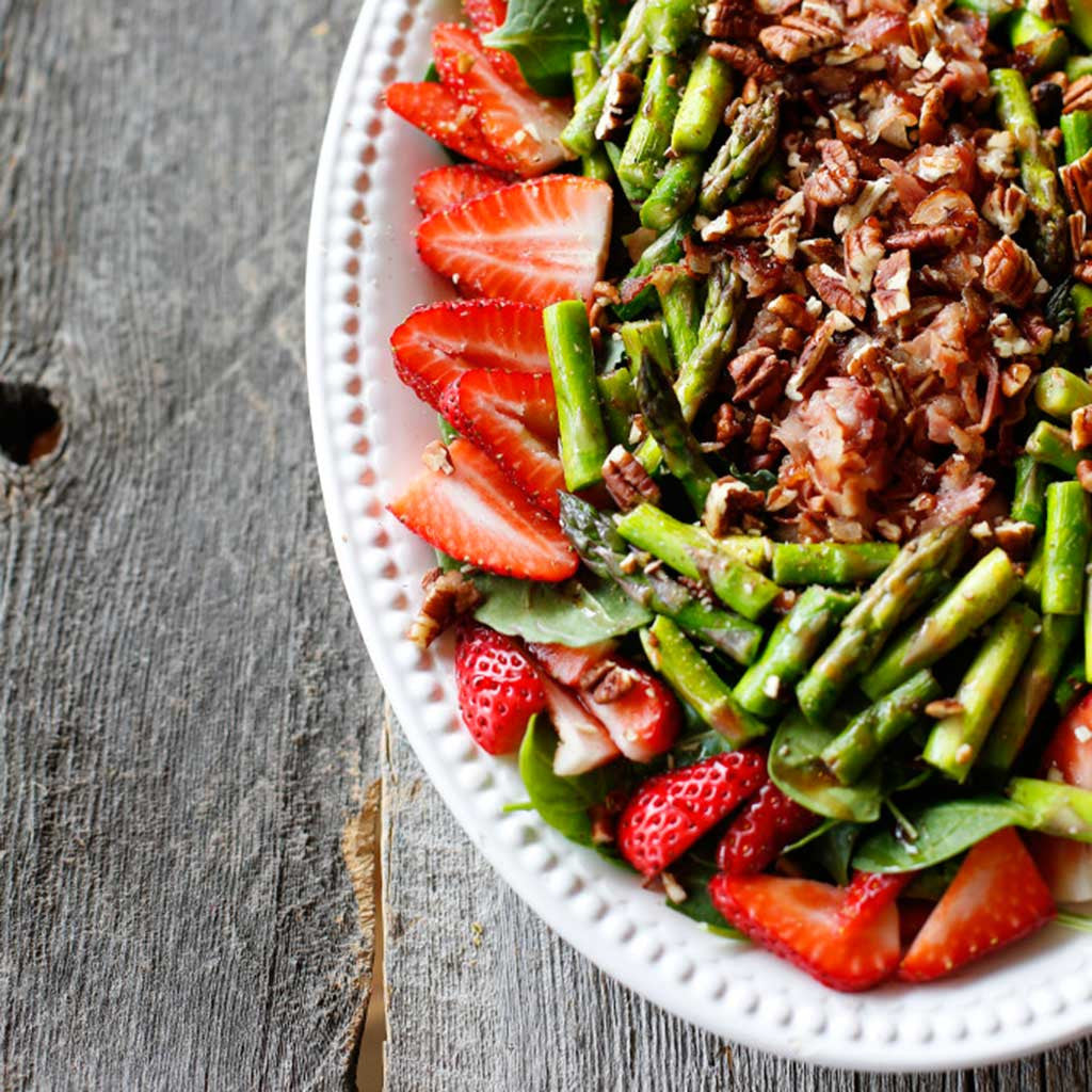 A colorful salad with strawberries, asparagus, drizzled with vinaigrette served in a white platter on a rustic, wood table.