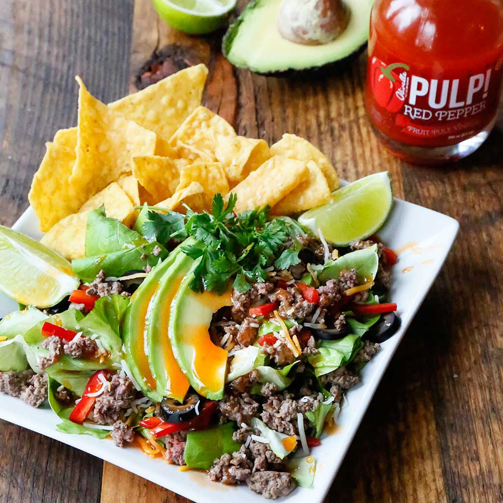 Red Pepper Taco Salad with side of avocados and tortilla chips served on a white square plate on a rustic table top next to avocado halves and Pulp! Red Pepper Fruit Pulp Vinegar