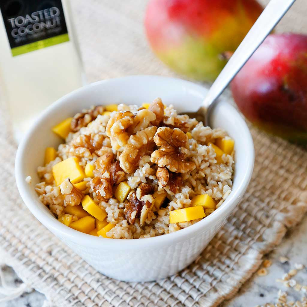 mango and walnut steel cut oats with toasted coconut balsamic vinegar served in a white bowl with a spoon