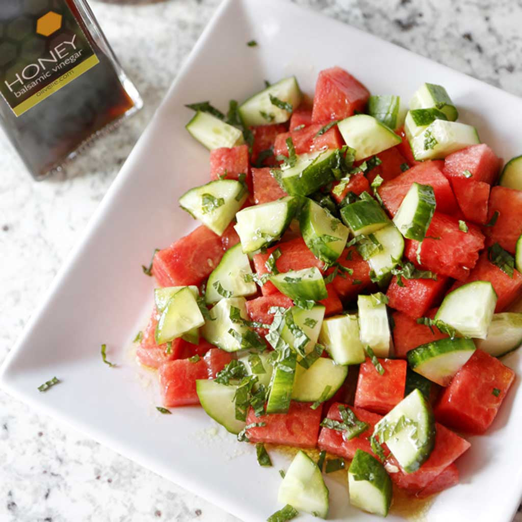 A light and refreshing side dish combining watermelon, cucumbers, mint leaves, our Honey Balsamic Vinegar and Sicilian Lemon or Basil Genovese Olive Oil served on a white salad plate next to a bottle of honey vinegar
