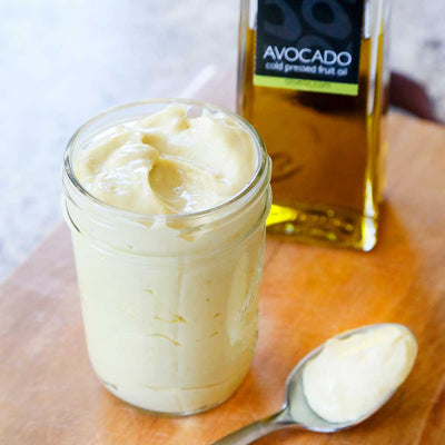 A mason jar of Avocado Oil Mayonnaise and a silver spoon next to a bottle of Avocado Oil (Extra Virgin, Cold-Pressed)