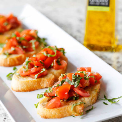 Tomato & Basil Bruscetta served on a white rectangular platter next to a bottle of Basil Genovese Infused Olive Oil on a marble counter top