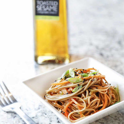 Garlic Sesame Soba Noodle Salad served in a white square bowl next to a bottle of Toasted Sesame Oil on a marble counter top