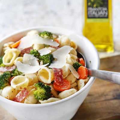 Italian Pasta Salad with a Classic Vinaigrette served in a white bowl on a wooden platter next to a bottle of Frantoia Italian Extra Virgin Olive Oil on a marble counter top