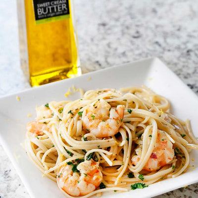 Shrimp Scampi served on a square white plate next to a bottle of Sweet Cream Butter Olive Oil on a marble counter top