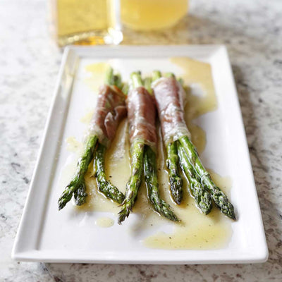 Pancetta-Wrapped Asparagus with Citrus Vinaigrette served on a white rectangular platter next to a bottle of White Balsamic Vinegar and Lemon Infused Olive Oil