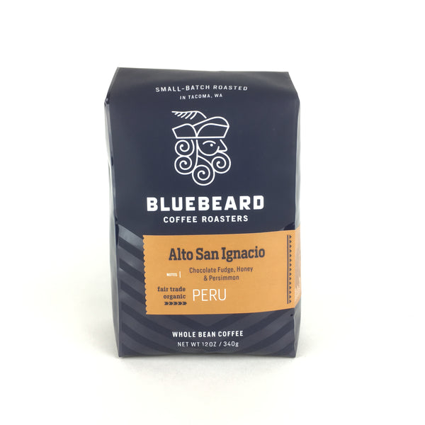 12oz bag of whole bean coffee from Alto San Ignacio, Cajamarca, Peru. Has a brown label with coffee name and additional coffee notes on a valve sealed navy blue bag with the Bluebeard Coffee Roasters logo and text.