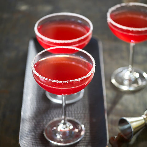 Cocktail coupes filled with a luscious red Cosmopolitan cocktail, placed on a modern grey tray
