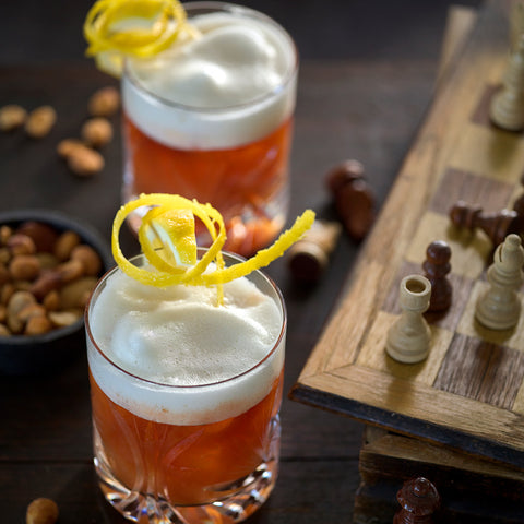 Two fluffly Whisky Sour cocktails in stylish Schott Zwiesel Old Fashioned Glasses. Sitting next to a chess board and bow of nuts for the perfecr afternoon of sipping.