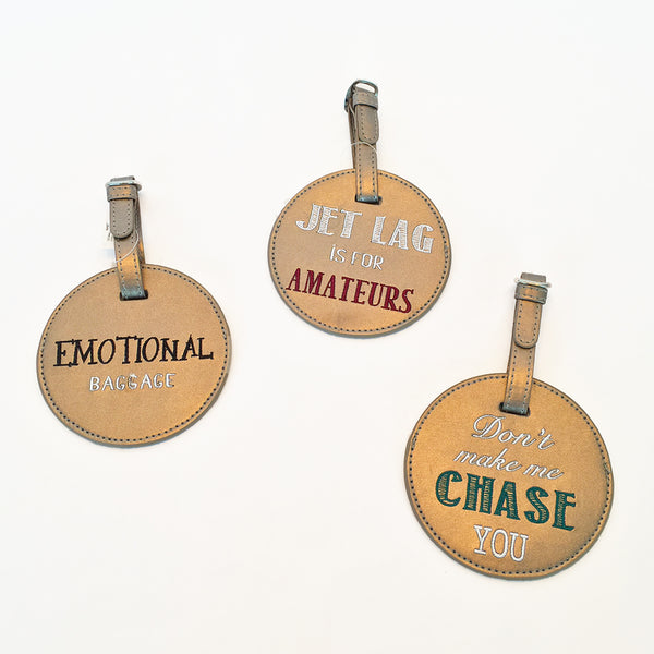 Round luggage tag made of bronze leatherette. Embroidered sayings on each. Strap with buckle