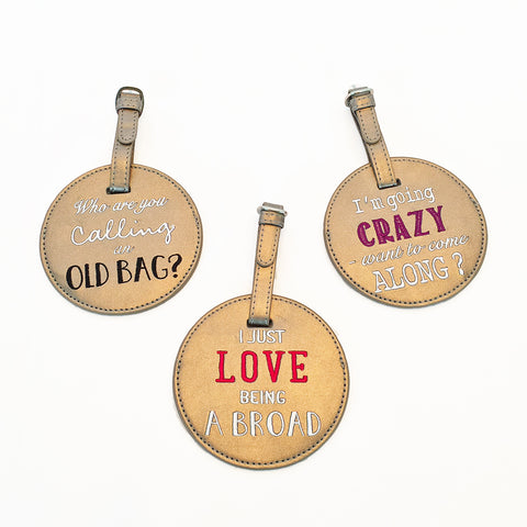 Round luggage tag made of bronze leatherette. Embroidered sayings on each. Back view showing security flap. Strap with buckle