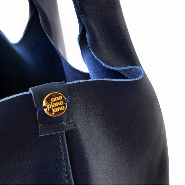 One Plane Jane Travel, Shopping Tote shown in blue leather.  Close up view of side seam and charm