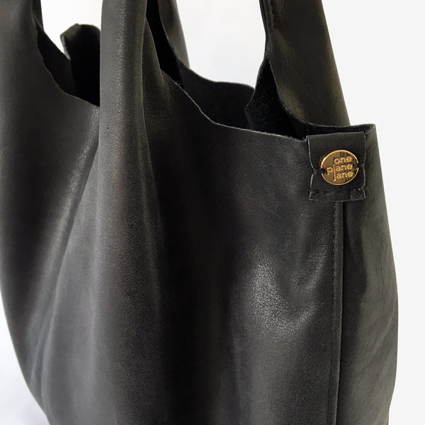 One Plane Jane Travel, Shopping Tote shown in charcoal leather.  Close up view of side seam and charm
