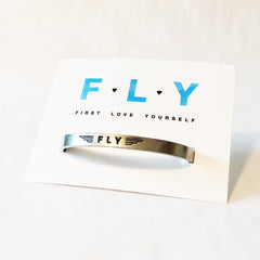 "FLY pewter adjustable cuff bracelet with backer card. ""FLY"" pictured with wings around it on the face and ""First Love Yourself"" on the inside of the cuff. White backer card stating the same."