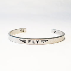 "FLY pewter adjustable cuff bracelet front view. ""FLY"" pictured with wings around it on the face"