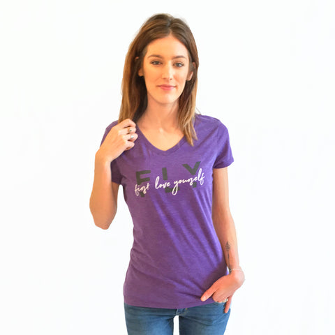 "One Plane Jane FLY First Love Yourself graphic tshirt tee. Shown in purple with ""FLY"" in dark purple print and ""first love yourself"" in white script print. V-Neck and short sleeves."