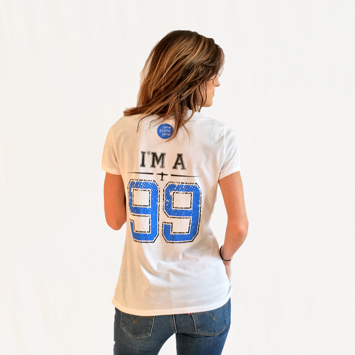 "One Plane Jane - I'm A 99 football style shirt.  Back view with ""99"" printed large as if a player's number.  Printed in bright blue and black.  One Plane Jane logo below collar"