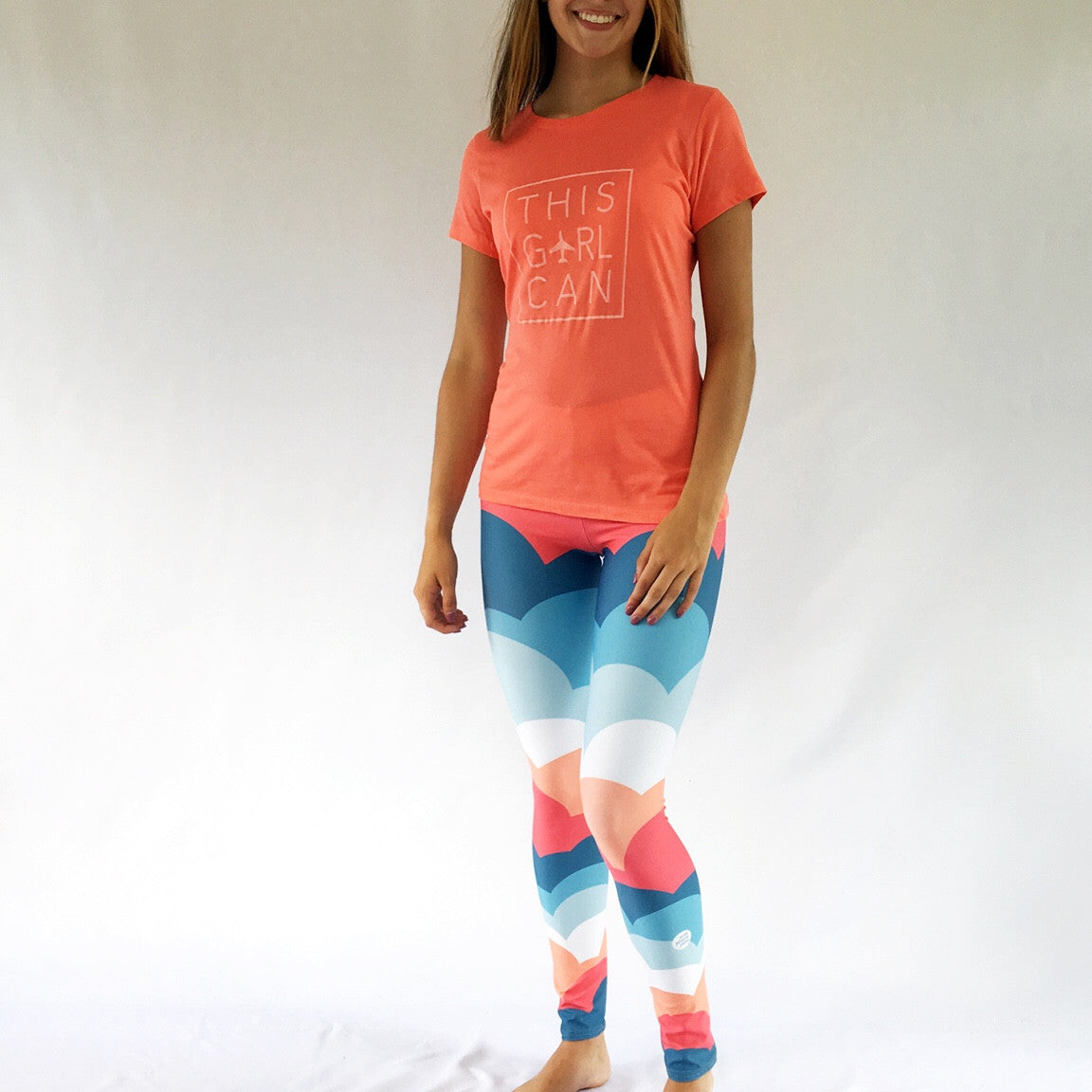 One Plane Jane signature cloud leggings. Fun blue, orange and coral design with an airplane on the back side of right leg. Cute, comfy and fun.  Perfect for aviators or anyone that loves to travel.