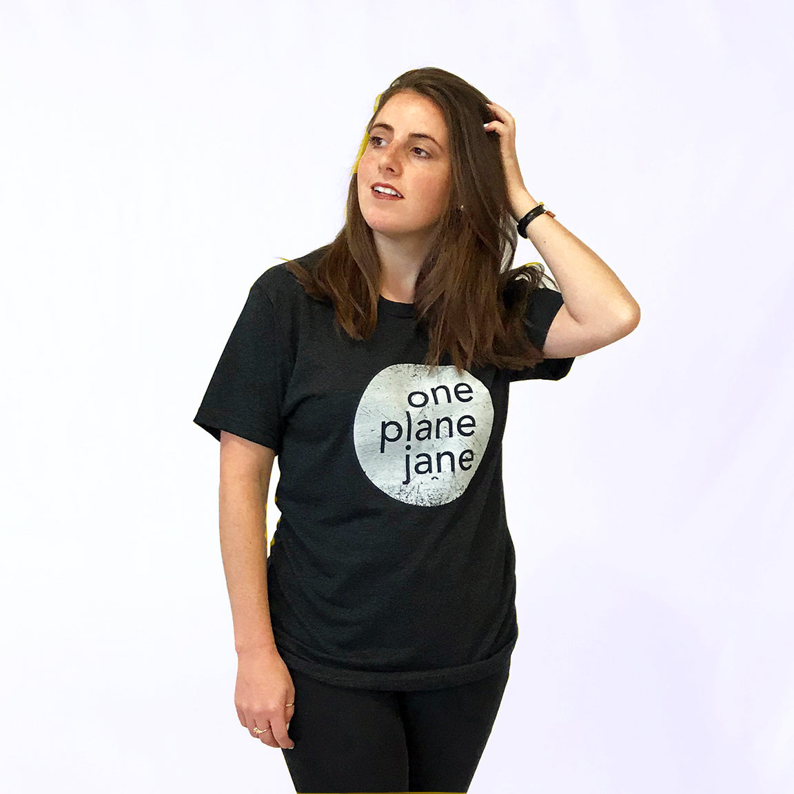 One Plane Jane Unisex logo tee t-shirt.  Show in black with a large white One Plane Jane logo
