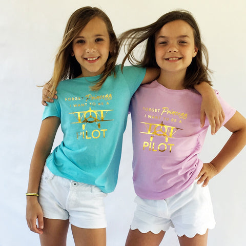 One Plane Jane Girls Tee - Forget Princess, I want to be a pilot.  Two young girls showing the cancun blue & lilac pink tees with gold leaf printing.