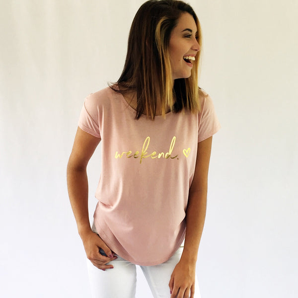 "One Plane Jane Golden Weekend Tee.  Show in Rose Quartz with ""Weekend"" and a heart printed in gold-leaf"